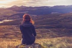 Mujer que se sienta en el top de la montaña y que comtempla