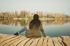 Mujer que se sienta en el topo de madera Foto de archivo libre de regalías