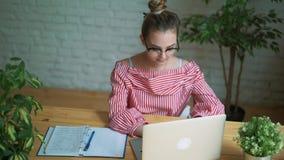 Mujer que se sienta en el trabajo en la tabla delante de un ordenador portátil, manos femeninas en el teclado almacen de video