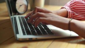 Mujer que se sienta en el trabajo en la tabla delante de un ordenador portátil, manos femeninas en el teclado metrajes