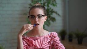 Mujer que se sienta en el trabajo en la tabla delante de un ordenador portátil, manos femeninas en el teclado almacen de metraje de vídeo