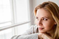 Mujer que se sienta en el travesaño de la ventana, mirando fuera de ventana Fotos de archivo
