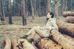 Mujer que se sienta en el tronco de árbol al aire libre Foto de archivo libre de regalías