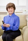 Mujer que se sienta en envío de mensajes de texto del sofá Foto de archivo libre de regalías