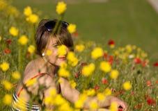 Mujer que se sienta en flores Fotografía de archivo