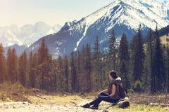 Mujer que se sienta en fondo natural de la montaña Imagen de archivo libre de regalías