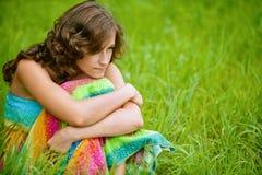Mujer que se sienta en hierba y el pensamiento Imagenes de archivo