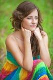 Mujer que se sienta en hierba y el pensamiento Foto de archivo libre de regalías