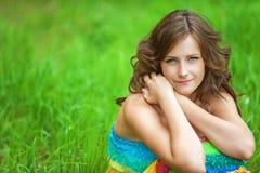 Mujer que se sienta en hierba y el pensamiento Imagen de archivo libre de regalías