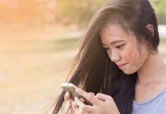 Mujer que se sienta en jardín usando un teléfono móvil Imagenes de archivo