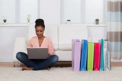 Mujer que se sienta en la alfombra que hace compras en línea fotografía de archivo
