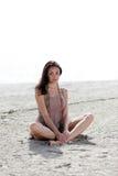 Mujer que se sienta en la arena Fotografía de archivo