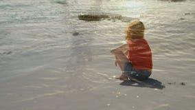 Mujer que se sienta en la arena almacen de video