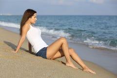 Mujer que se sienta en la arena de la playa Fotos de archivo