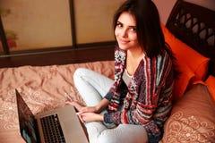 Mujer que se sienta en la cama con el ordenador portátil Foto de archivo libre de regalías