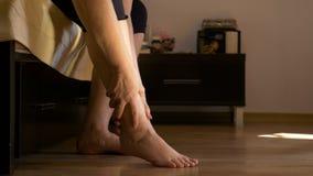 Mujer que se sienta en la cama que hace masaje de las piernas del uno mismo en su dormitorio almacen de metraje de vídeo