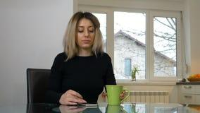 Mujer que se sienta en la cocina y que enrolla el teléfono mientras que bebe el café almacen de metraje de vídeo