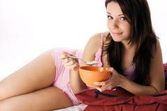 Mujer que se sienta en la consumición de la cama Imagen de archivo