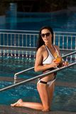 Mujer que se sienta en la entrada de una piscina con el cóctel foto de archivo