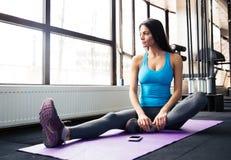 Mujer que se sienta en la estera de la yoga Fotografía de archivo