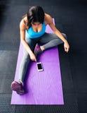Mujer que se sienta en la estera de la yoga y que mira en smartphone Imágenes de archivo libres de regalías