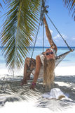 Mujer que se sienta en la hamaca Foto de archivo libre de regalías