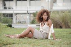 Mujer que se sienta en la hierba fotos de archivo libres de regalías