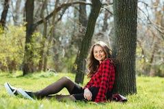 Mujer que se sienta en la hierba al aire libre Fotos de archivo libres de regalías