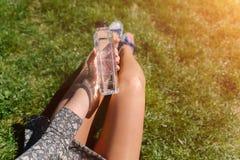 Mujer que se sienta en la hierba con una botella de agua y del badmin dos Imagen de archivo