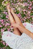 Mujer que se sienta en la hierba cubierta con los pétalos y las flores rosados del cerezo fotografía de archivo