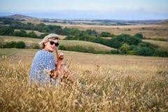 Mujer que se sienta en la hierba est?ril seca, mirando la c?mara fotografía de archivo