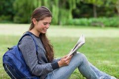Mujer que se sienta en la hierba mientras que lee un libro Foto de archivo libre de regalías