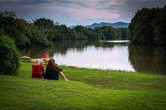 Mujer que se sienta en la hierba que pasa por alto el lago Foto de archivo
