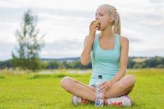 Mujer que se sienta en la hierba y que come la manzana después de entrenamiento Foto de archivo libre de regalías