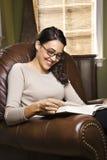 Mujer que se sienta en la lectura de la silla Fotos de archivo