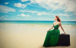 Mujer que se sienta en la maleta que disfruta de vista al mar Fotografía de archivo