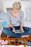 Mujer que se sienta en la maleta sobrecargada mientras que usa la tableta de Digitaces imagenes de archivo