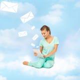Mujer que se sienta en la nube con PC de la tableta Imagen de archivo