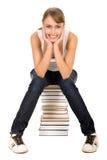 Mujer que se sienta en la pila de libros Fotografía de archivo libre de regalías