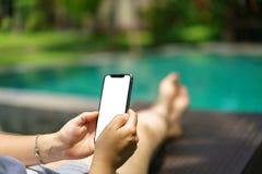Mujer que se sienta en la piscina tropical de la silla de cubierta que sostiene el teléfono elegante negro con la pantalla en bla imagen de archivo libre de regalías