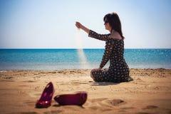 Mujer que se sienta en la playa Imagenes de archivo