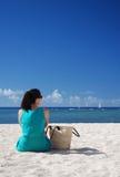 Mujer que se sienta en la playa Foto de archivo libre de regalías