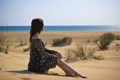 Mujer que se sienta en la playa Fotos de archivo