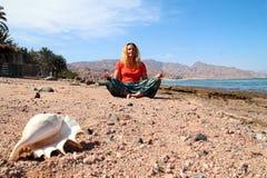Mujer que se sienta en la playa Imagen de archivo libre de regalías