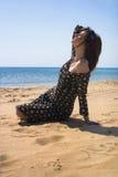 Mujer que se sienta en la playa con los ojos cerrados Imagen de archivo libre de regalías