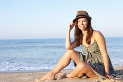 Mujer que se sienta en la playa que se relaja Foto de archivo libre de regalías