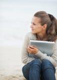 Mujer que se sienta en la playa sola y que abraza el ordenador portátil Imagen de archivo libre de regalías