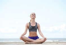 Mujer que se sienta en la posición de la yoga y que sonríe al aire libre Fotografía de archivo