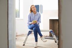 Mujer que se sienta en la propiedad que es renovada Fotos de archivo libres de regalías