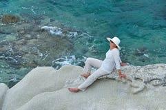 Mujer que se sienta en la roca cerca del mar Foto de archivo libre de regalías